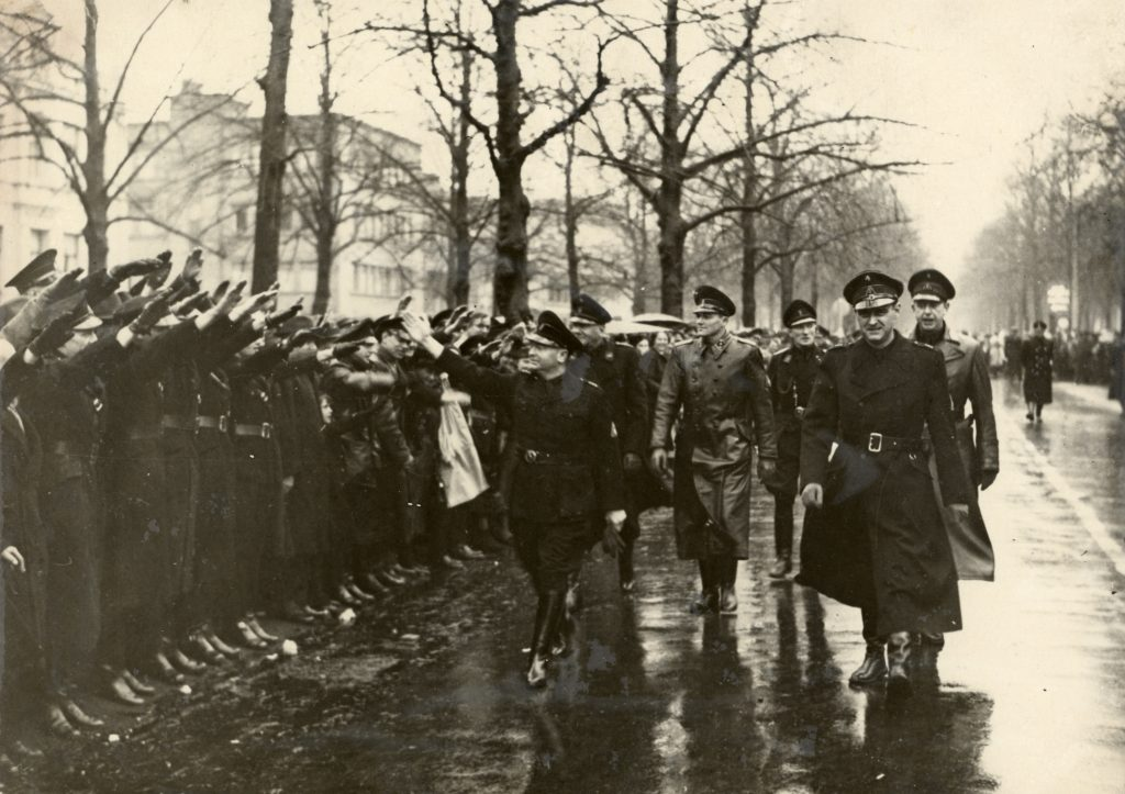 Afbeelding van Anton Mussert, leider van de NSB, die leden van de Weerafdeling groet tijdens een parade op de Maliebaan ter gelegenheid van het 10-jarig bestaan van de NSB. Rechts naast hem plaatsvervangend leider Cornelis van Geelkerken. Bron: Utrechts Archief 97890.