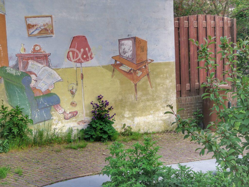 Muurschildering van Jos Peeters uit 1997 van een man met pantoffels aan die de krant leest. Lauwerecht 22, Utrecht.