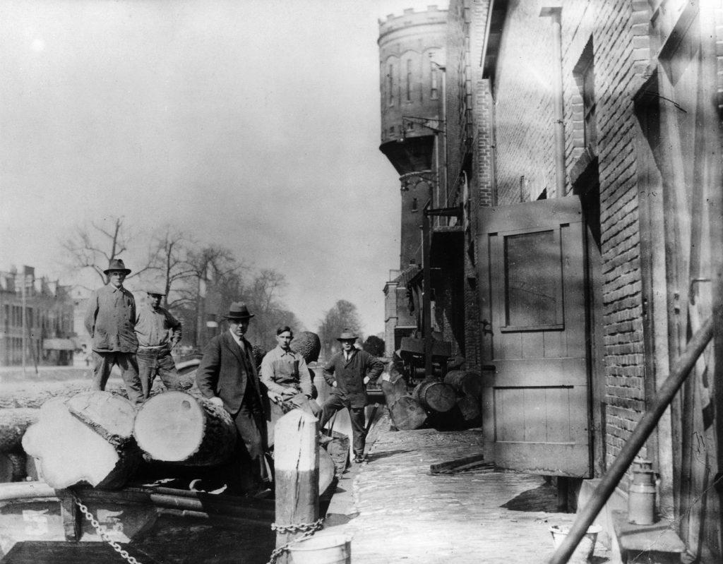 Foto van rond 1938: gezicht op de losplaats aan de achterkant van de Utrechtse Machinale Stoel- en Meubelfabriek vanuit het zuiden. Op de achtergrond de watertoren.