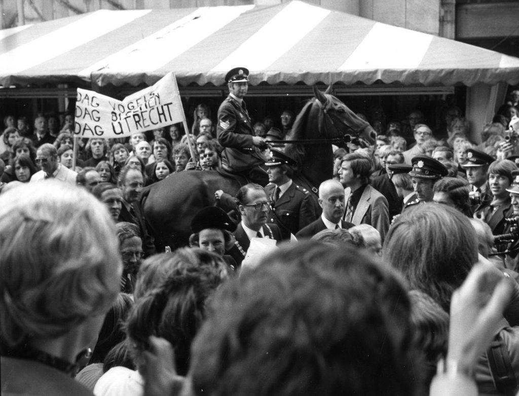 1973: het publiek op het Vredenburg te Utrecht tijdens de opening van Hoog Catharijne, met in het midden Beatrix en burgemeester Van Tuyll van Serooskerken. Op de achtergrond een spandoek van een groep tegenstanders van het winkelcentrum.
