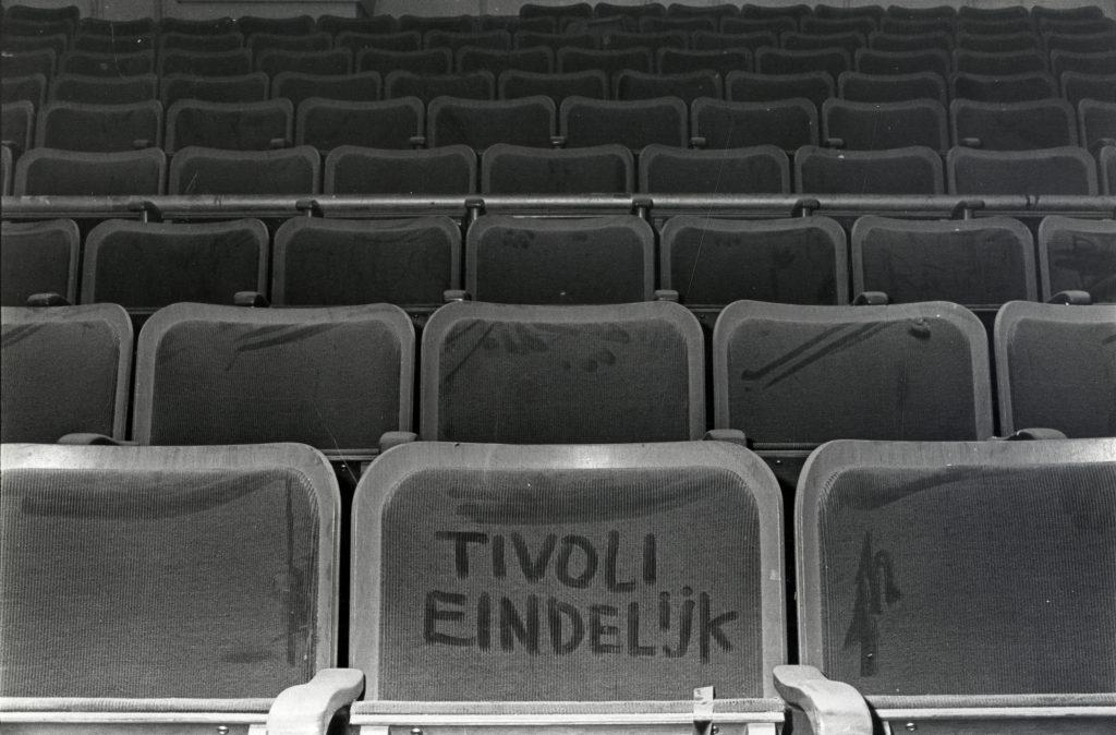 """Het voormalige N.V.-huis (Oudegracht 245) te Utrecht: tribune van het balkon, met in het stof op één van de zittingen geschreven de tekst """"Tivoli eindelijk""""."""